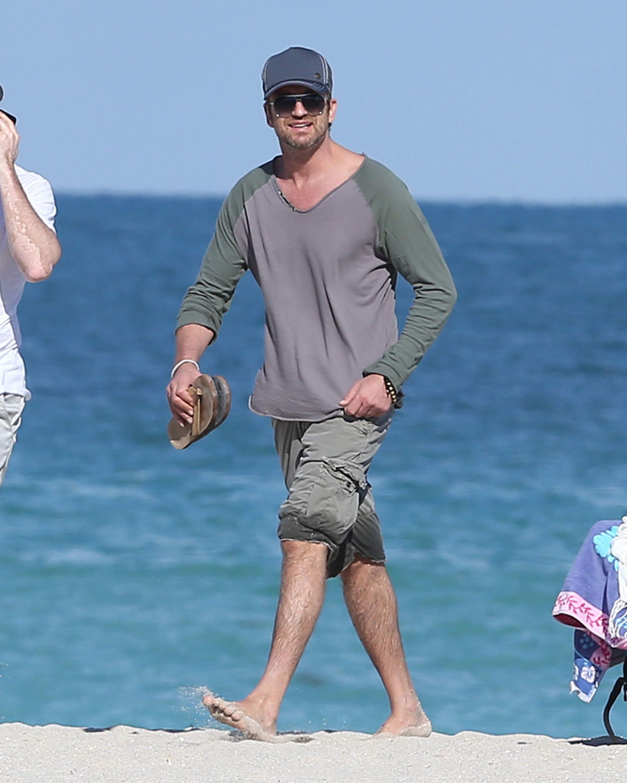 Gerard Butler gray shirt green shorts beach