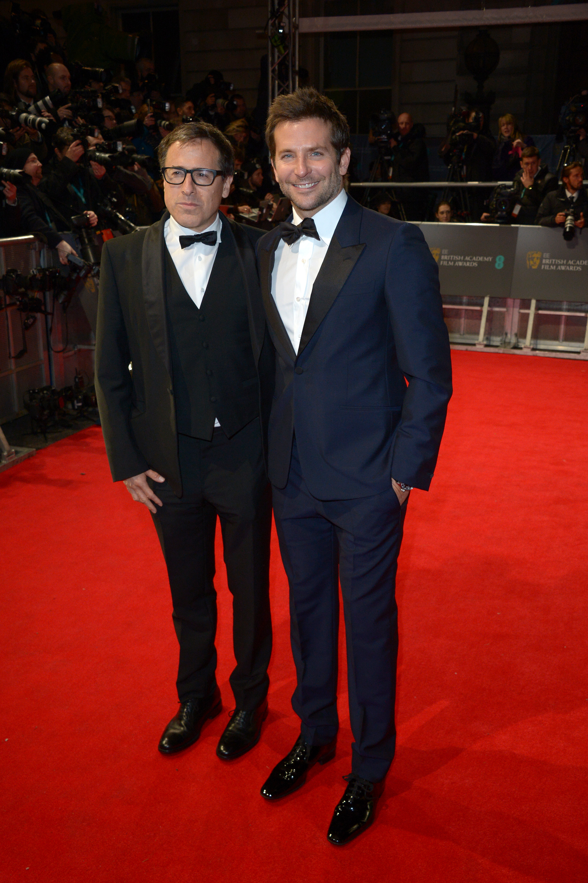 Director David O. Russell and actor Bradley Cooper pose for photographers on the red carpet at the EE British Academy Film Awards in London on Feb. 16, 2014.