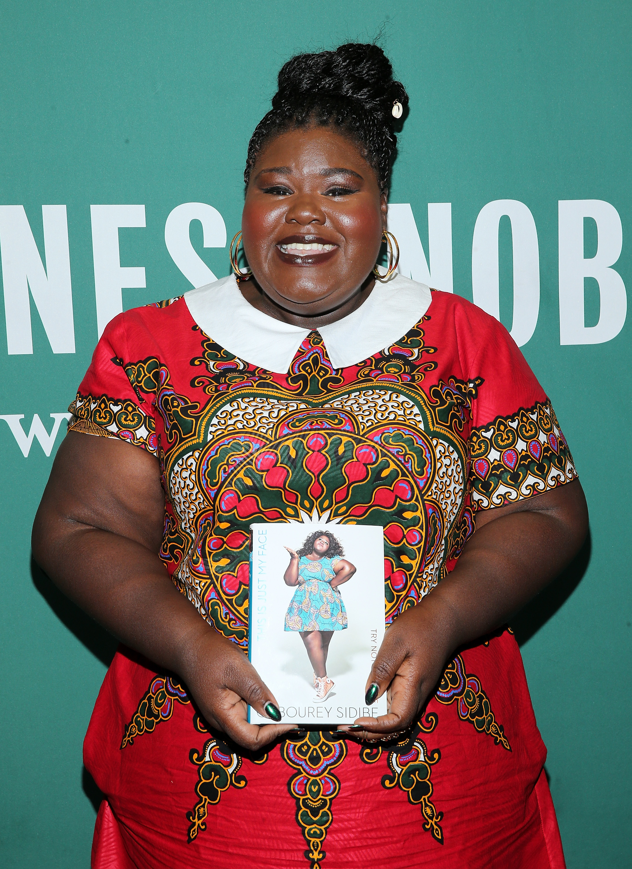 """Gabourey Sidibe poses for a photo with a copy of her new book """"This Is Just My Face: Try Not To Stare"""" during an in store appearance at Barnes & Noble Union Square in New York City on May 1, 2017."""