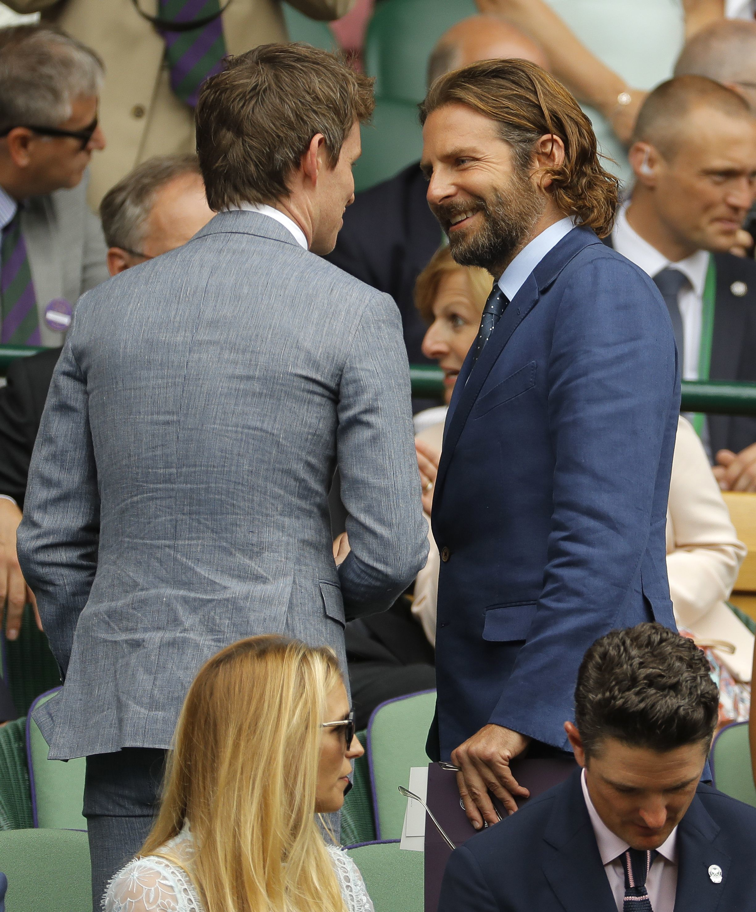 Eddie Redmayne chats with Bradley Cooper before taking his seat in the royal box for the men's singles final match between Switzerland's Roger Federer and Croatia's Marin Cilic on Day 13 at the Wimbledon Tennis Championships in London on July 16, 2017.