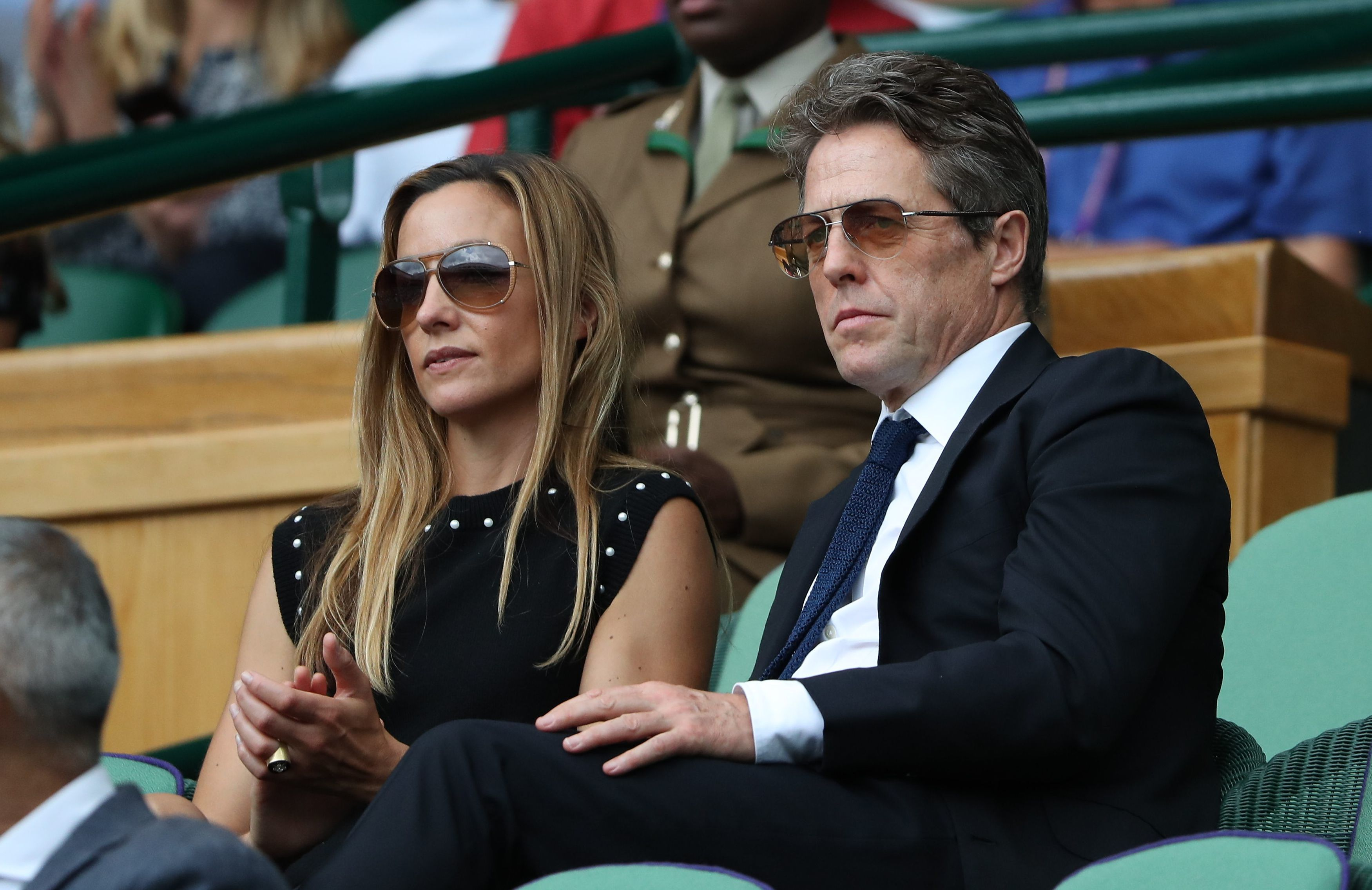 Hugh Grant and Anna Eberstein sit in the royal box on Day 13 of the Wimbledon Tennis Championships at the All England Lawn Tennis and Croquet Club in London on July 16, 2017.