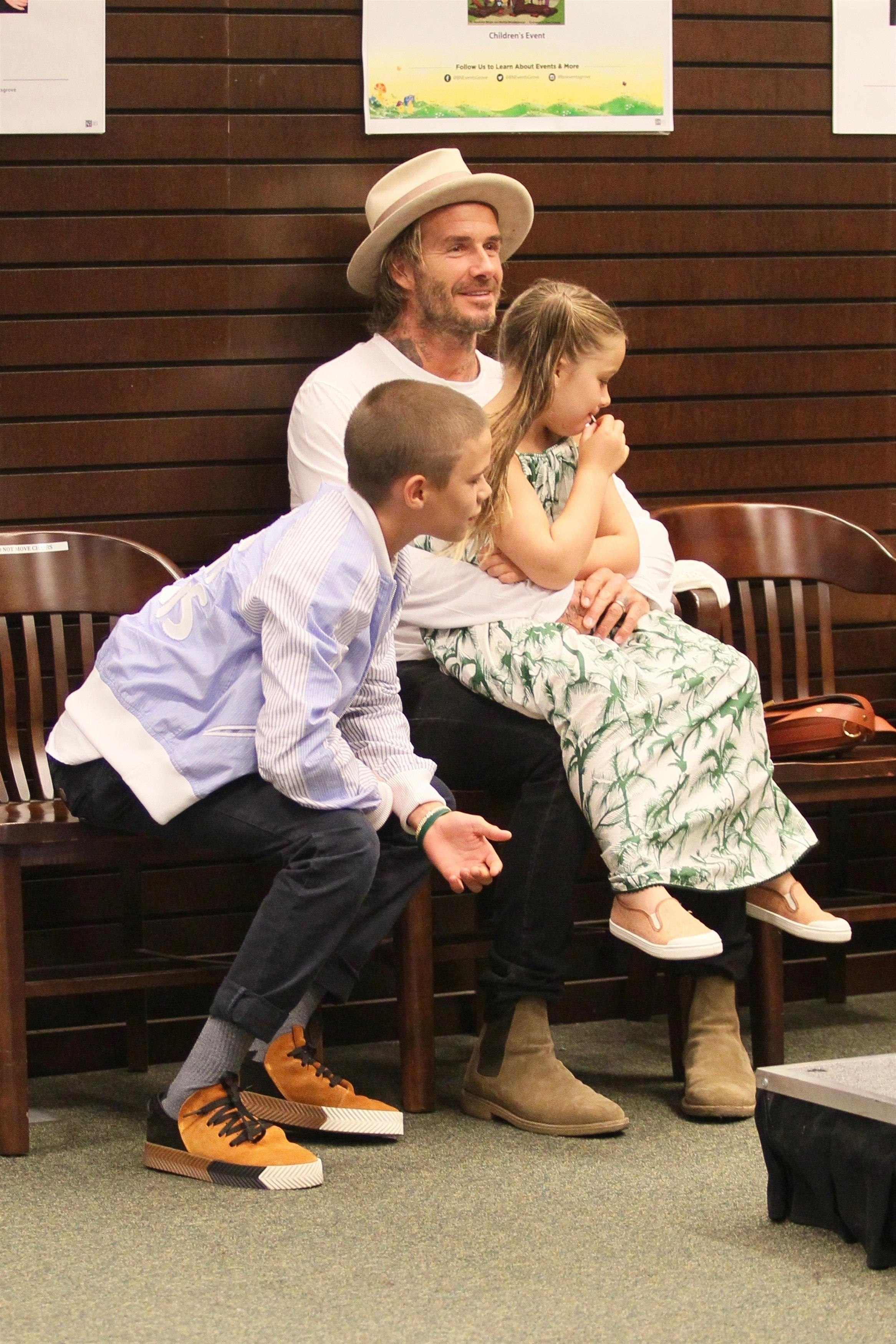David Beckham had his hands full with kids Romeo and Harper at son Brooklyn Beckham's photo book signing in Los Angeles on Aug. 2, 2017.