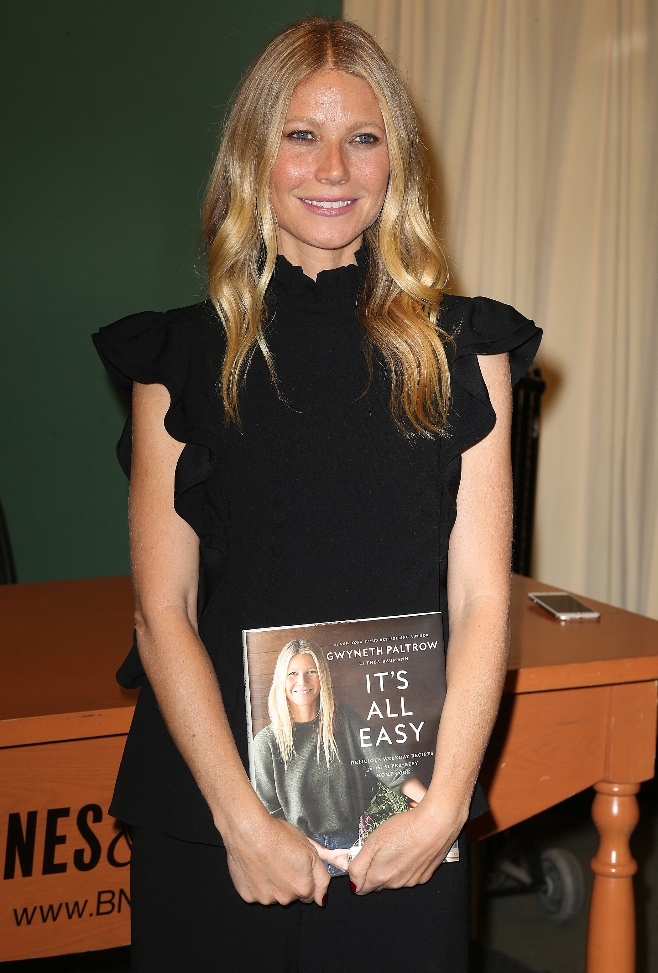 """Gwyneth Paltrow poses with her new cookbook """"It's All Easy"""" in New York on April 12, 2016."""