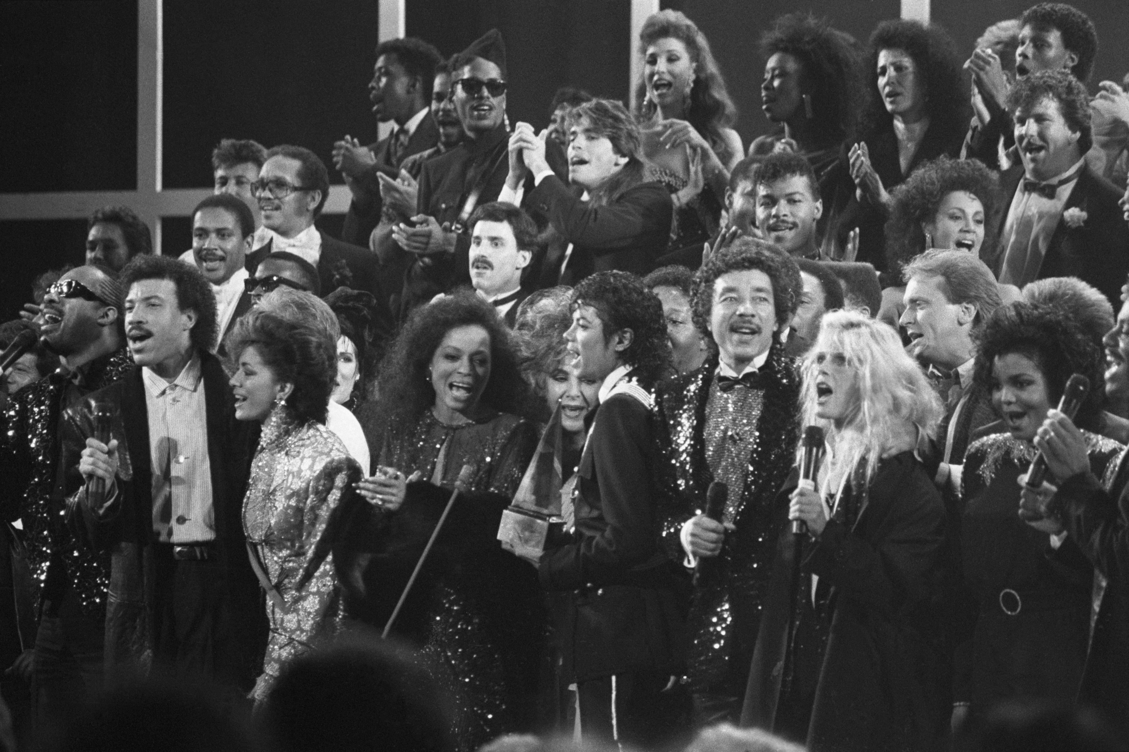 """A variety of music and movie stars sing """"We Are The World"""" a song written to benefit famine victims in Ethiopia. Across the front row stands: Stevie Wonder, Lionel Richie, Sheila E., Diana Ross, Elizabeth Taylor, Michael Jackson, Smokey Robinson, Kim Carnes, Michael Douglas, and Janet Jackson at the show held in 1986."""