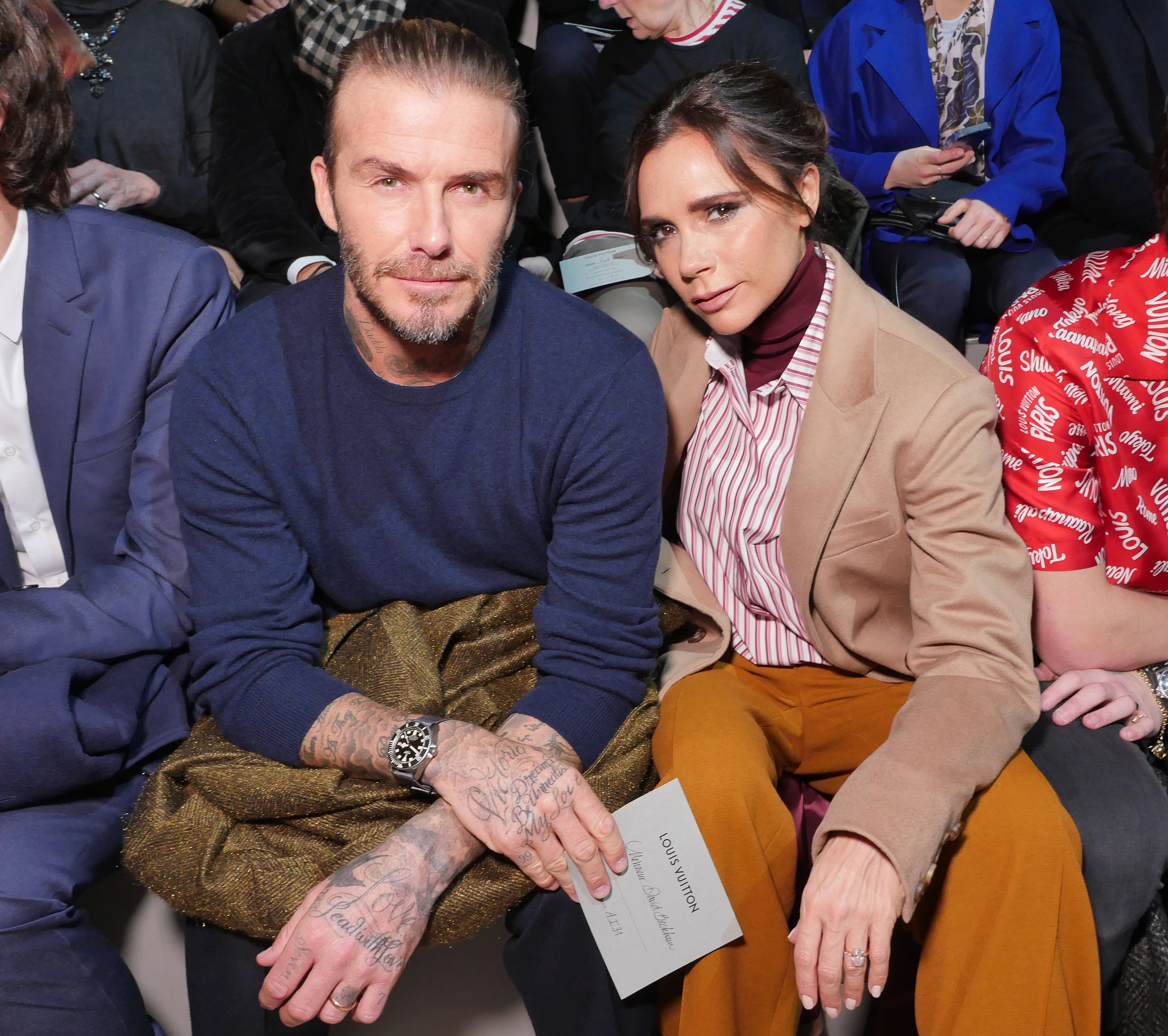 David Beckham and Victoria Beckham sits in the front row of the