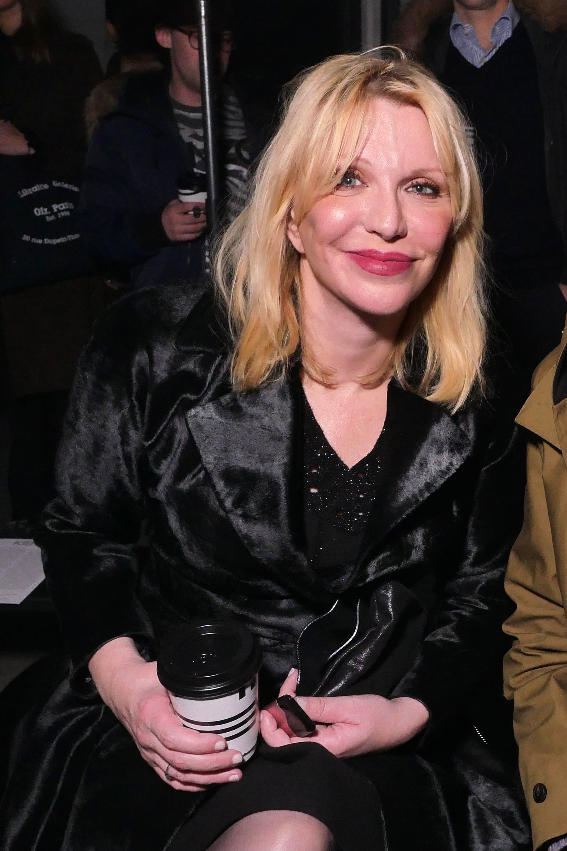 Courtney Love sits in the front row of the Kenzo show for Fall/Winter 2018 at Paris Fashion Week Men's on Jan. 21, 2018.