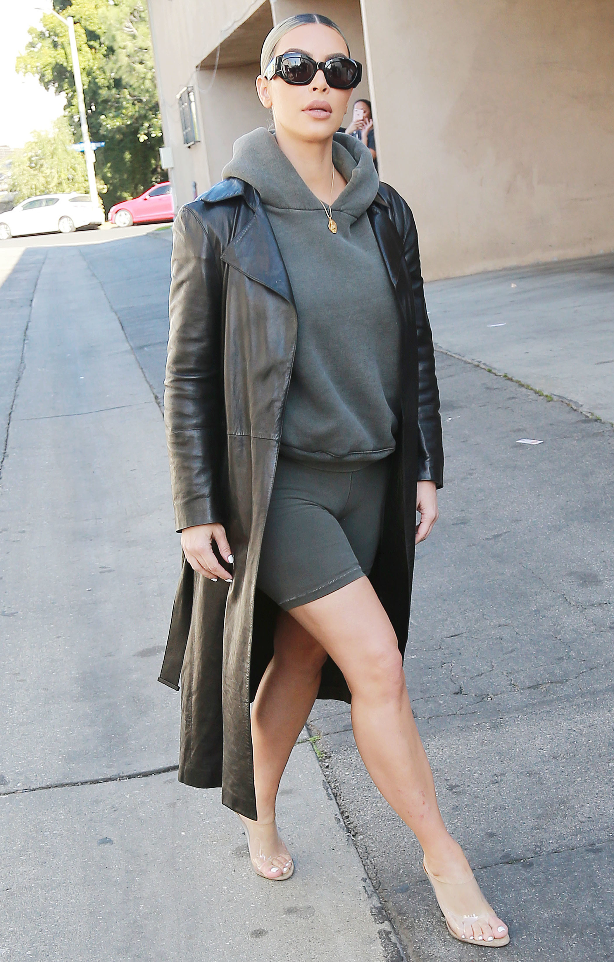 Kim Kardashian West shows off her toned legs in biker shorts and leather trenchcoat as she stops by DASH store in Los Angeles on Feb. 7, 2018.