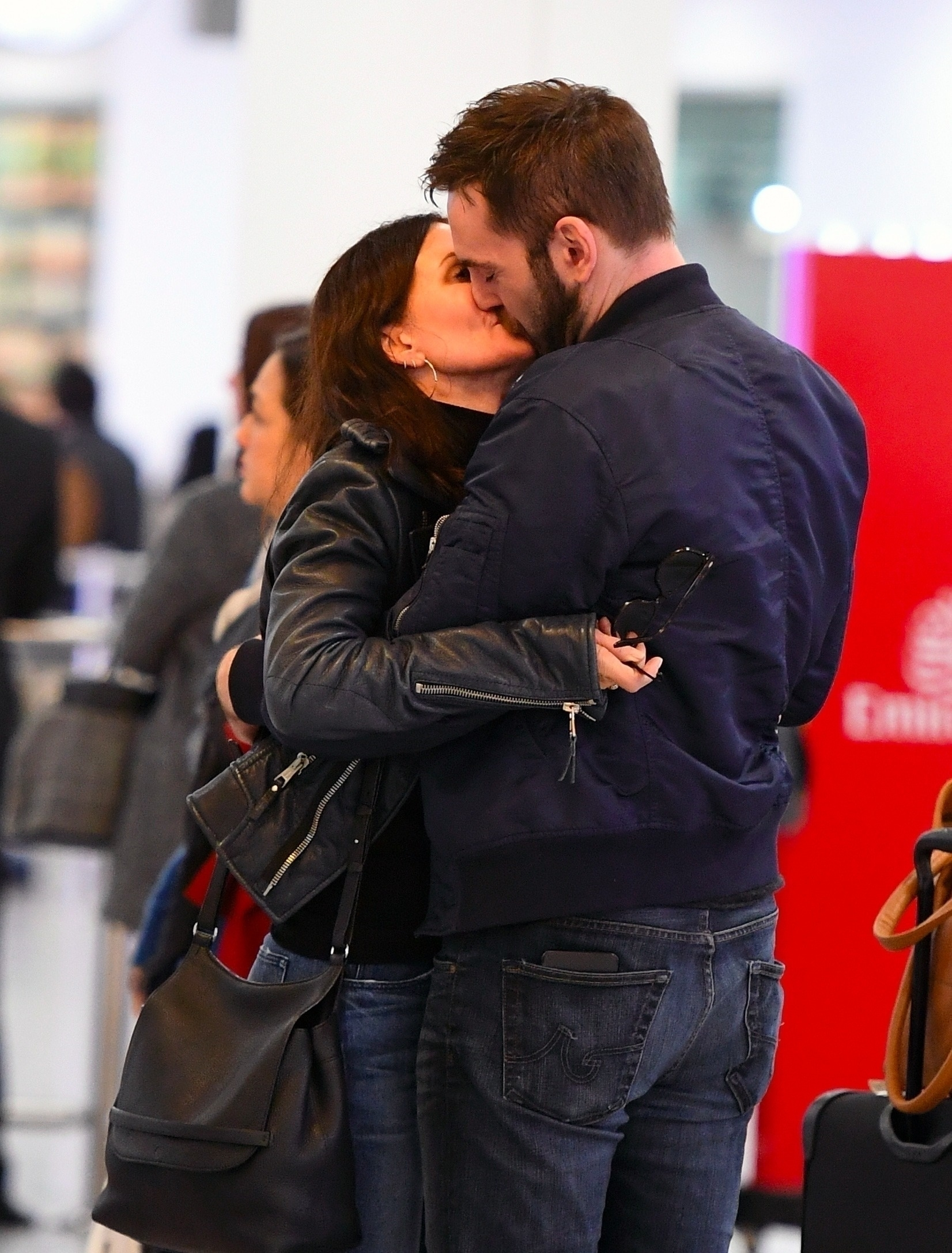 Courteney Cox and her fiance Johnny McDaid packed on the PDA on arrival at Heathrow Airport in London, England on Feb. 17, 2018.