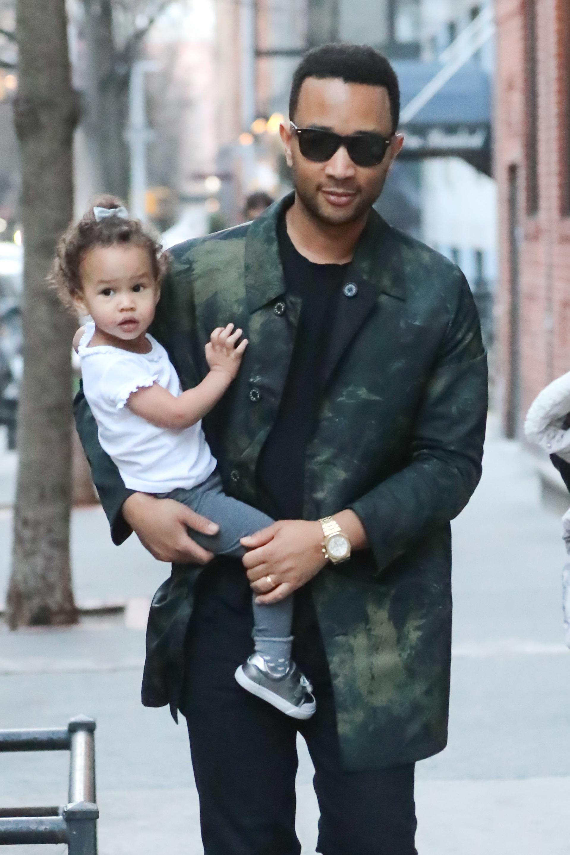 John Legend carries daughter Luna Stephens in New York City on Feb. 20, 2018.
