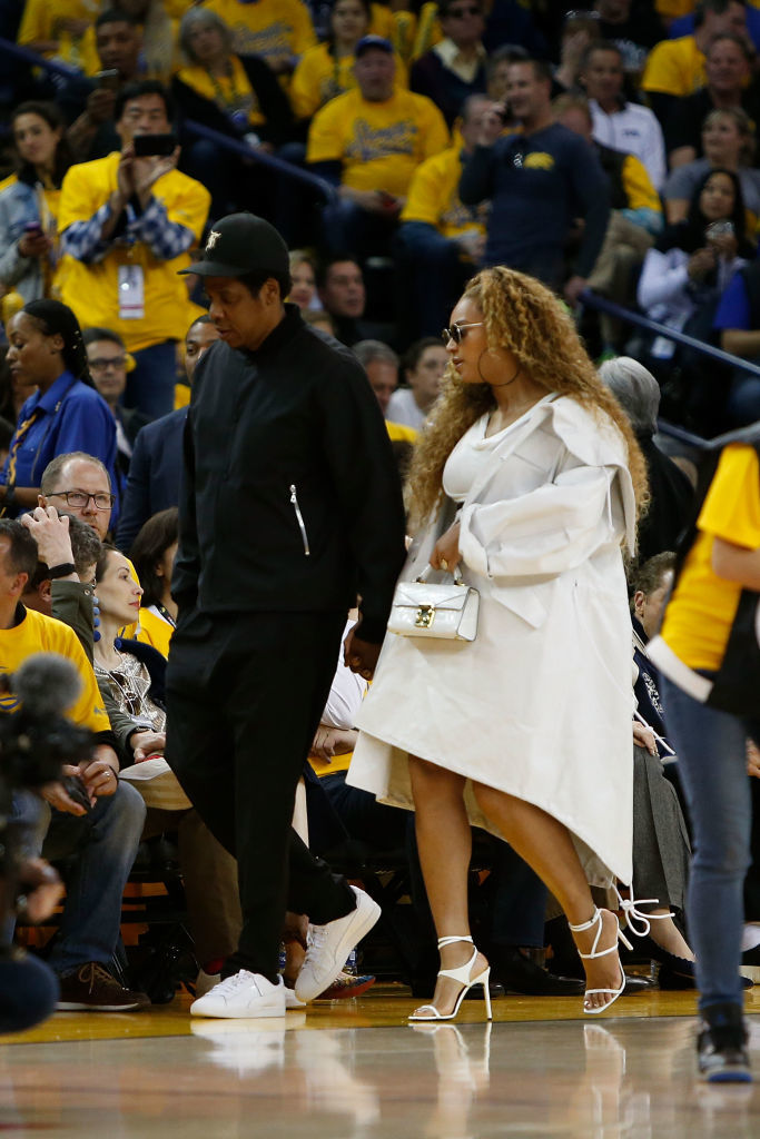 JAY Z and Beyonce make their way to their seats during Game One of the Western Conference Semifinals between the New Orleans Pelicans and the Golden State Warriors in Oakland, California, on April 28, 2018 .