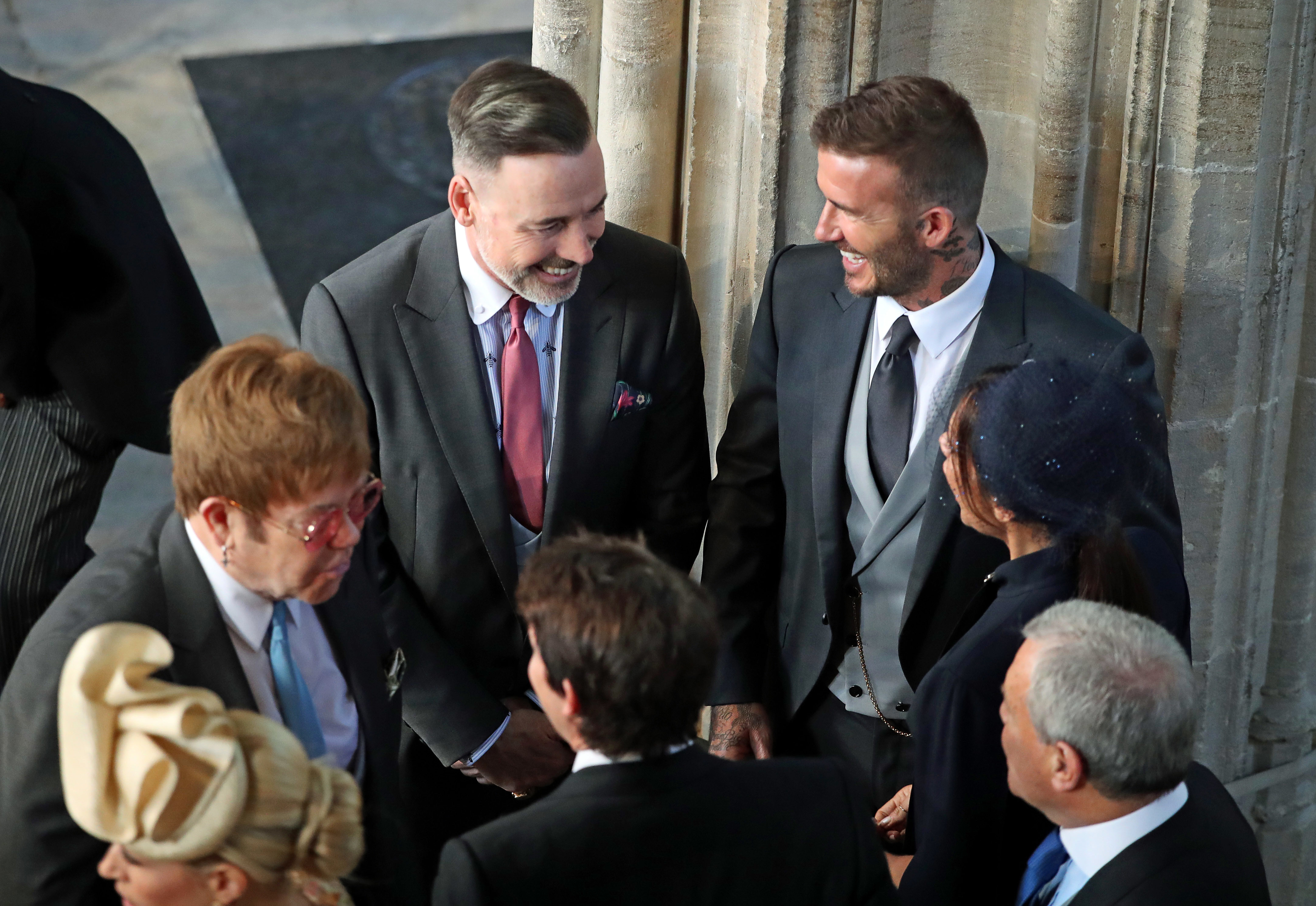 David Beckham and Victoria Beckham talk with Sir Elton John and husband David Furnish before the wedding of Prince Harry and Meghan Markle at St. George's Chapel at Windsor Castle on May 19, 2018.
