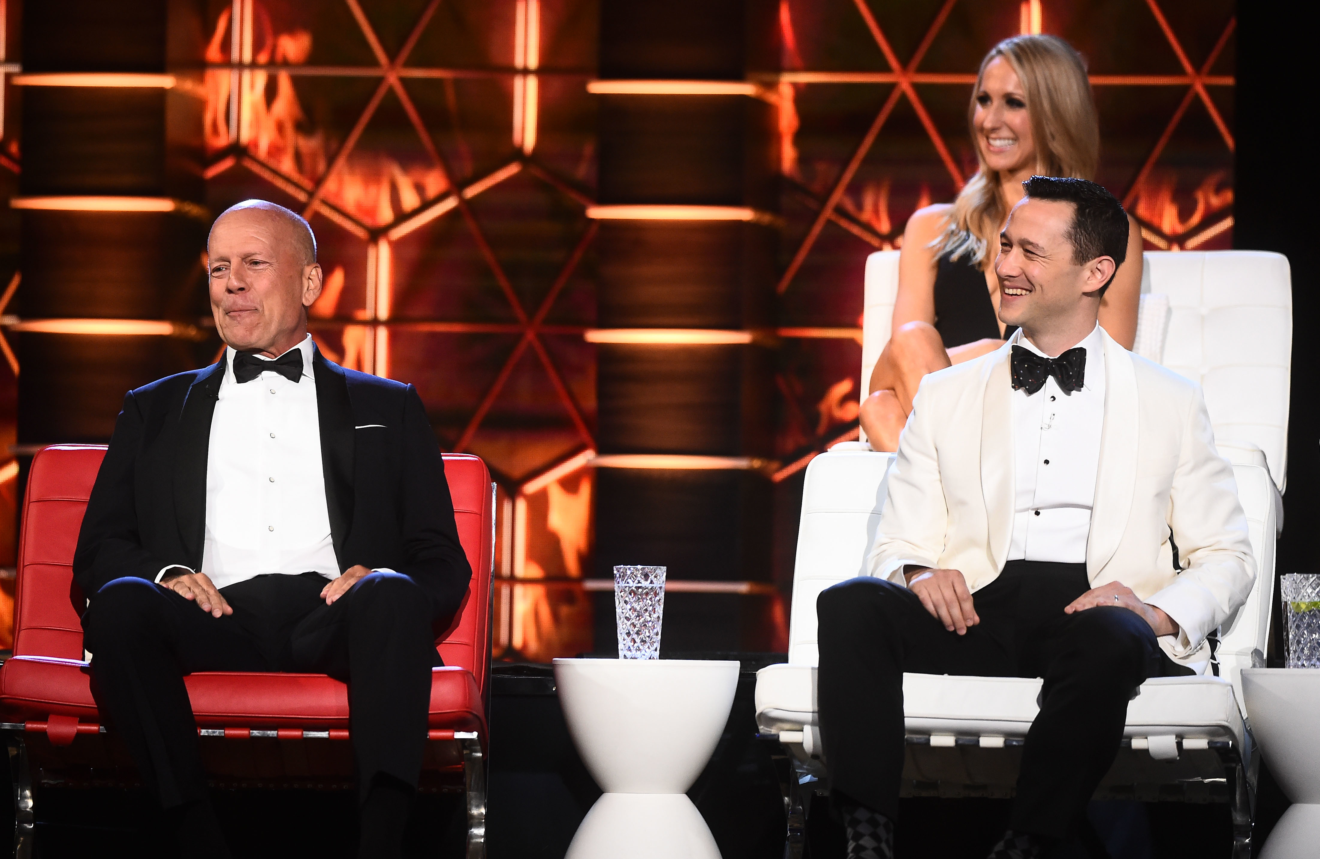 """Bruce Willis and Joseph Gordon Levitt sit on stage during the """"Comedy Central Roast of Bruce Willis"""" at the Hollywood Palladium on July 14, 2018."""