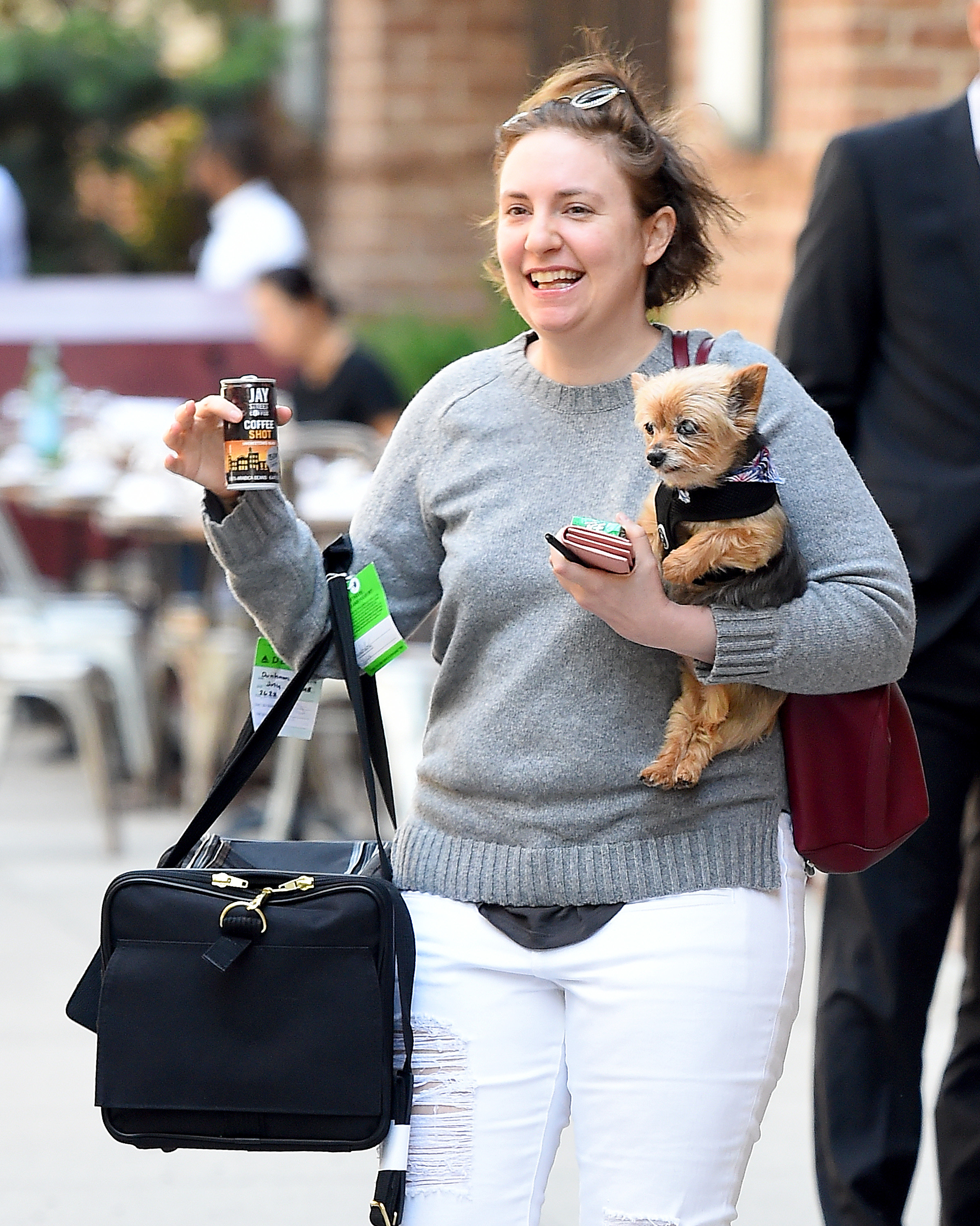 Lena Dunham looked happy as a clam while carrying her beloved dog around in New York City on July 26, 2018.