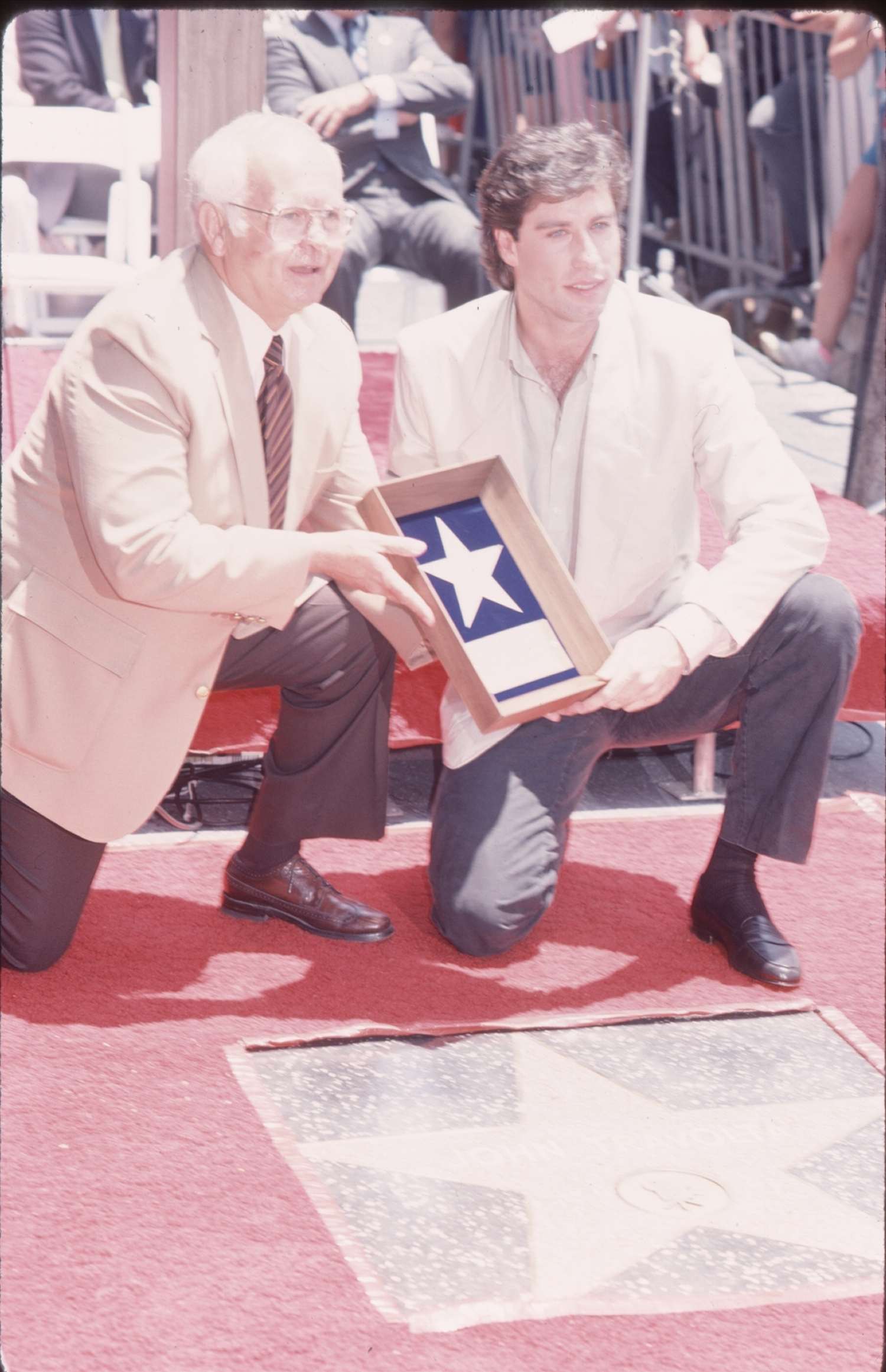 John Travolta poses with his star at his Hollywood Walk of Fame ceremony on June 5, 1985.