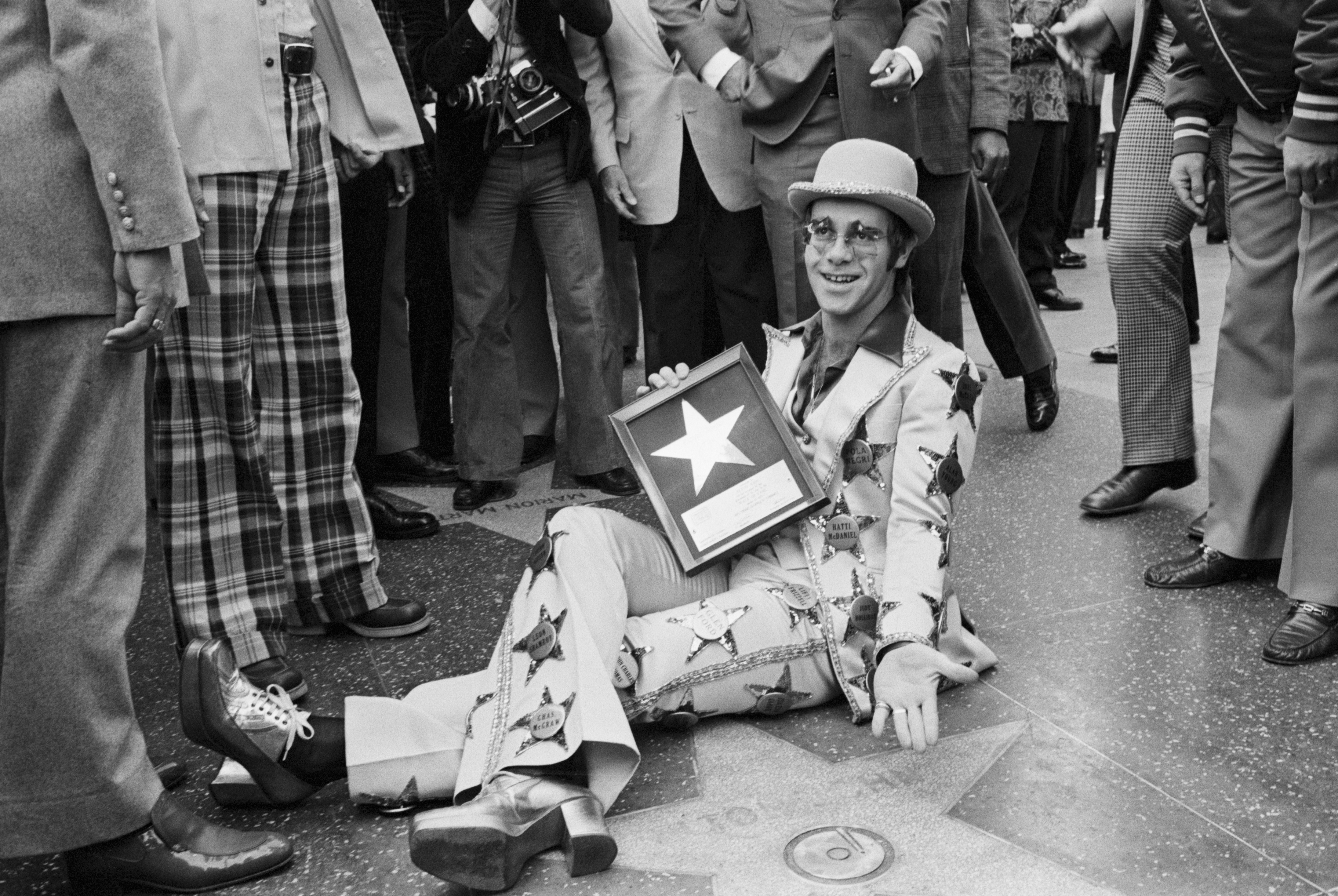 Elton John poses alongside his star on the Hollywood Walk of Fame in Los Angeles on Oct. 24, 1975.