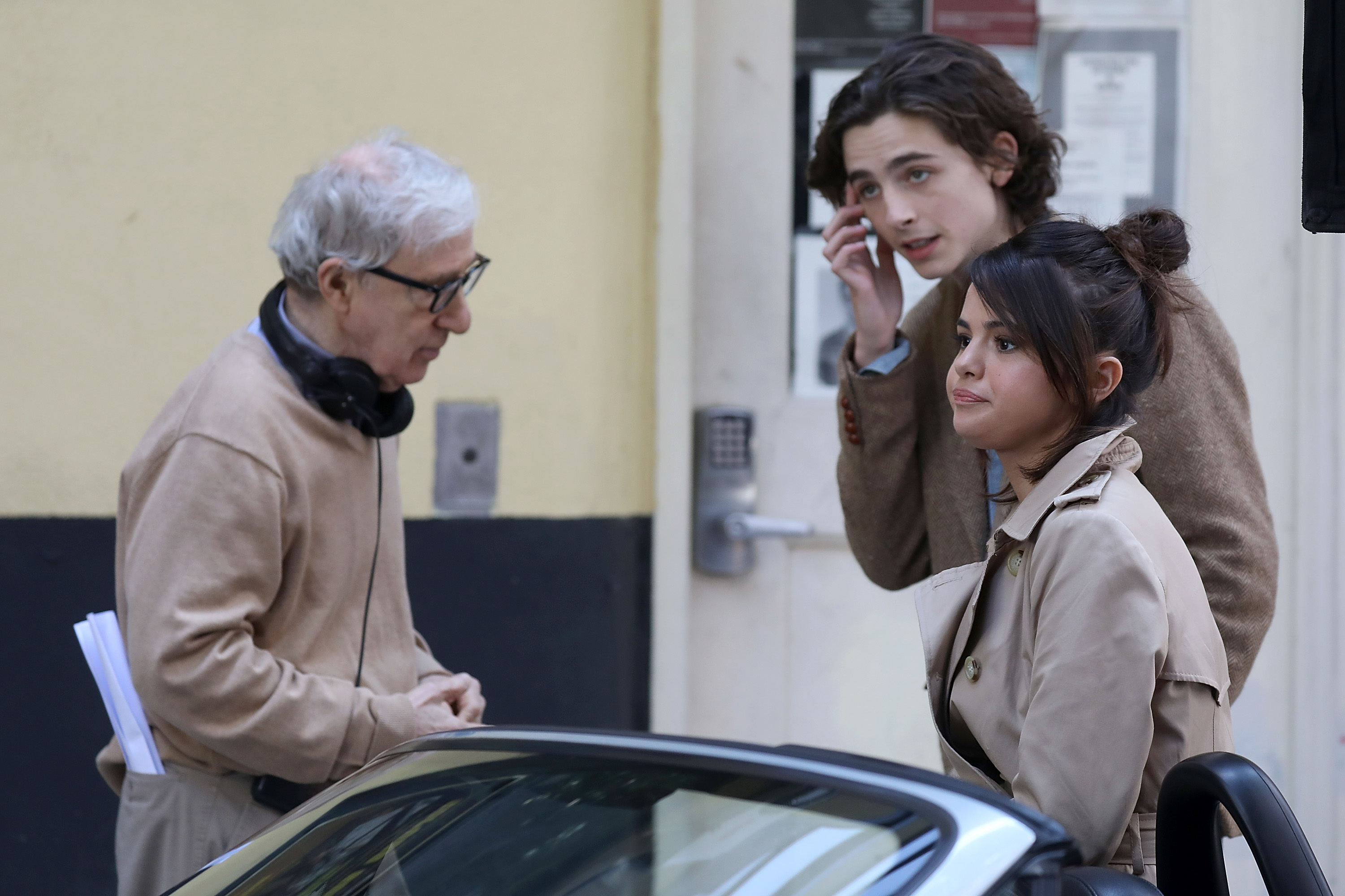 """Selena Gomez and Timothee Chalamet speak to director Woody Allen on the set of """"A Rainy Day in New York"""" on Sept. 11, 2017."""