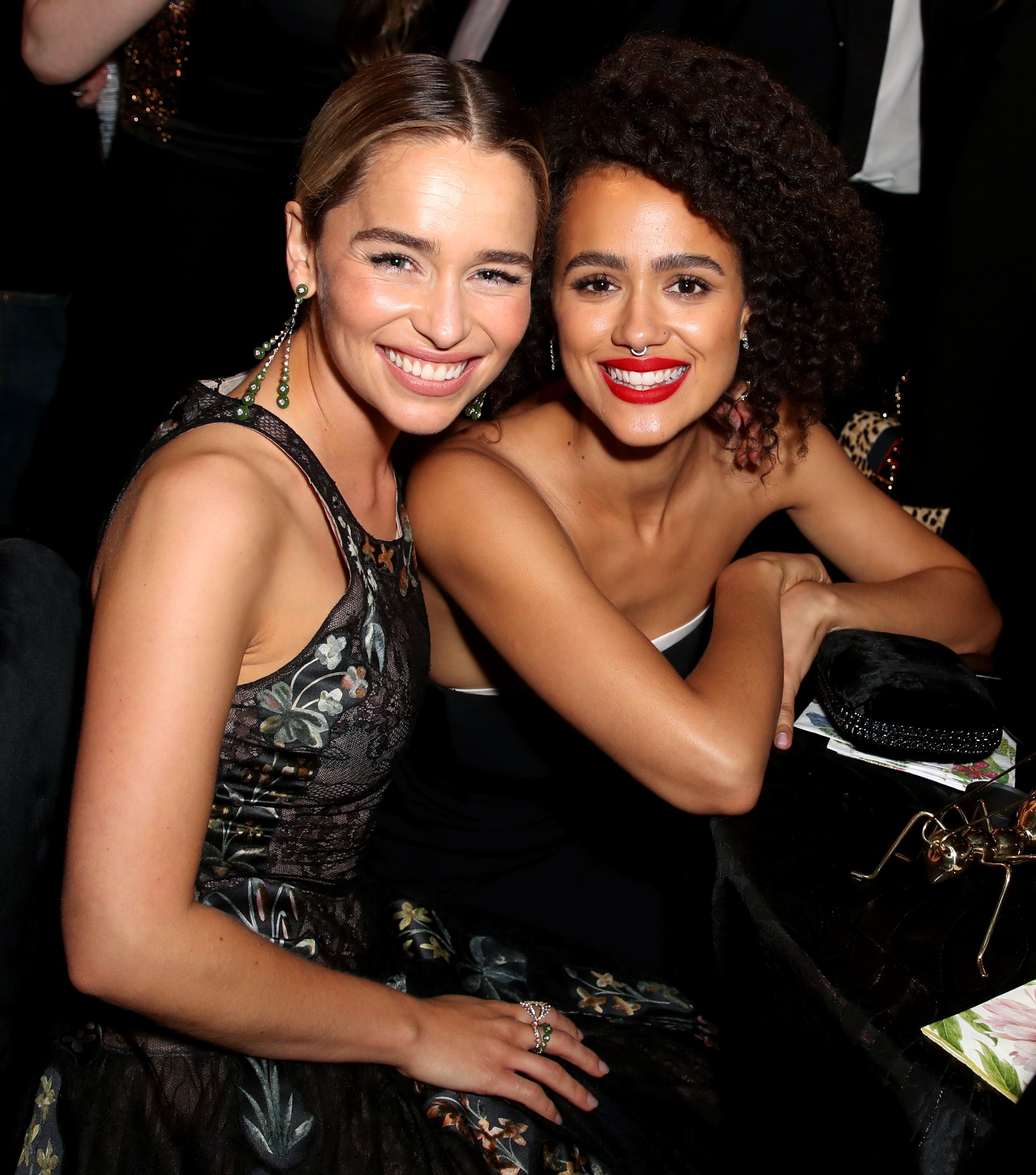 """""""Game of Thrones"""" co stars Emilia Clarke and Nathalie Emmanuel sit together at HBO's Emmys afterparty in Los Angeles on Sept. 17, 2018."""