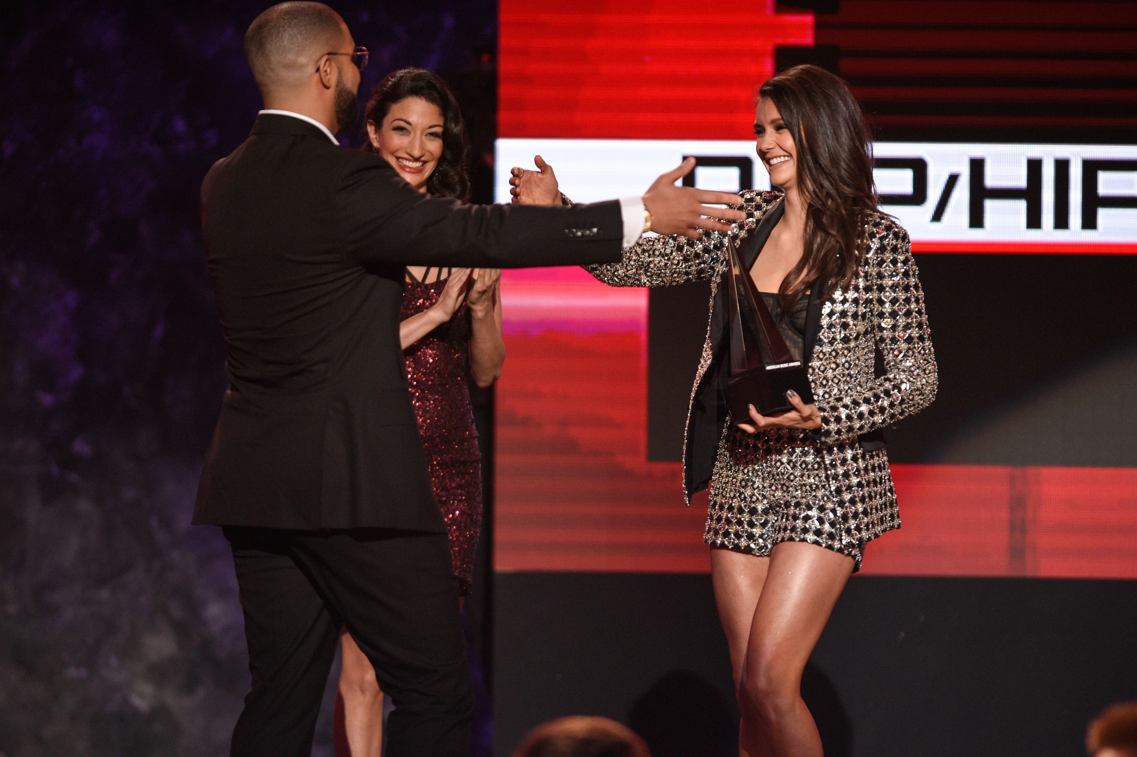 Nina Dobrev presents Drake with an awards at the American Music Awards in Los Angeles on Nov. 20, 2016.