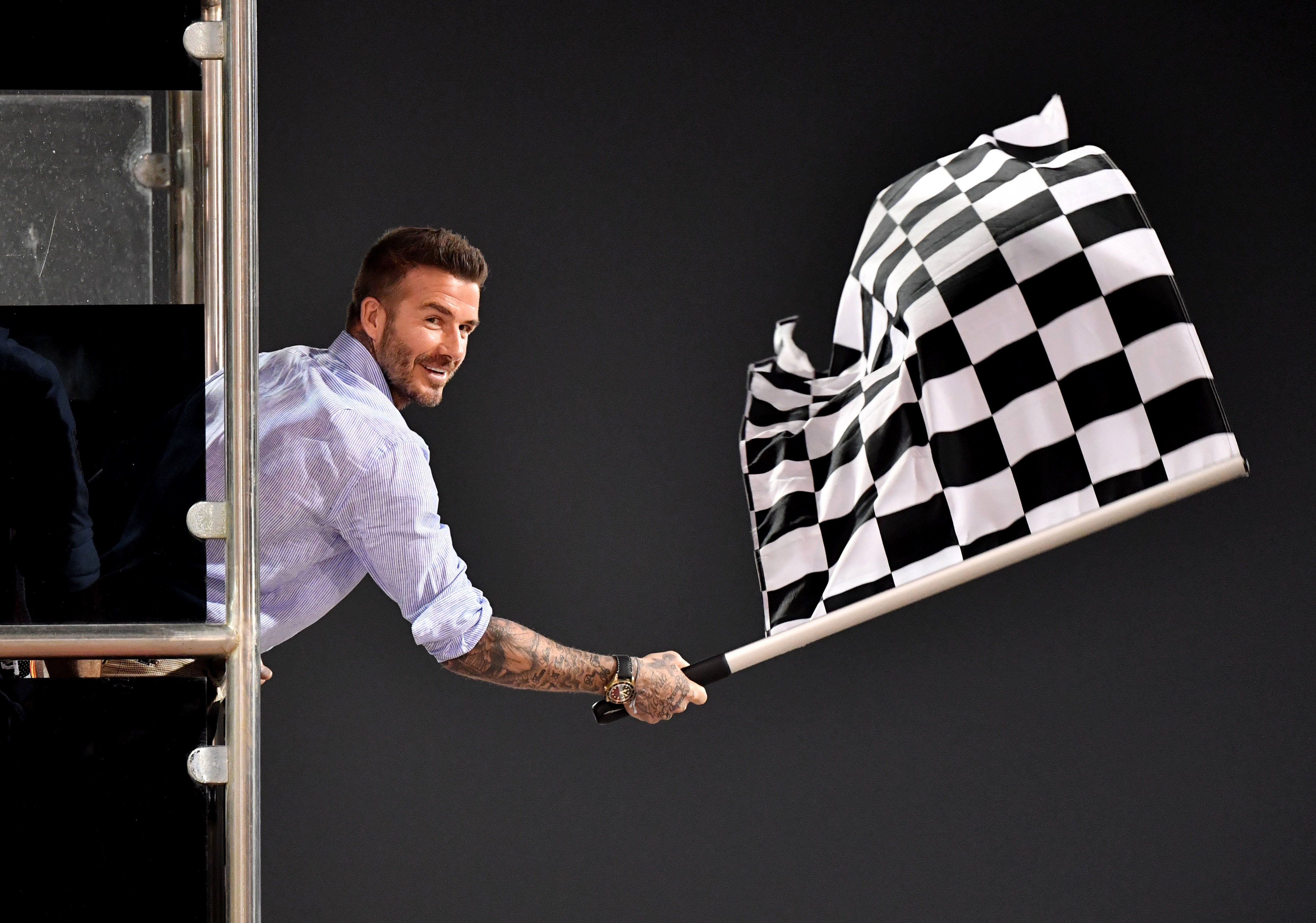 David Beckham waves the checkered flag during the Formula One Bahrain Grand Prix in Manama on March 31, 2019.