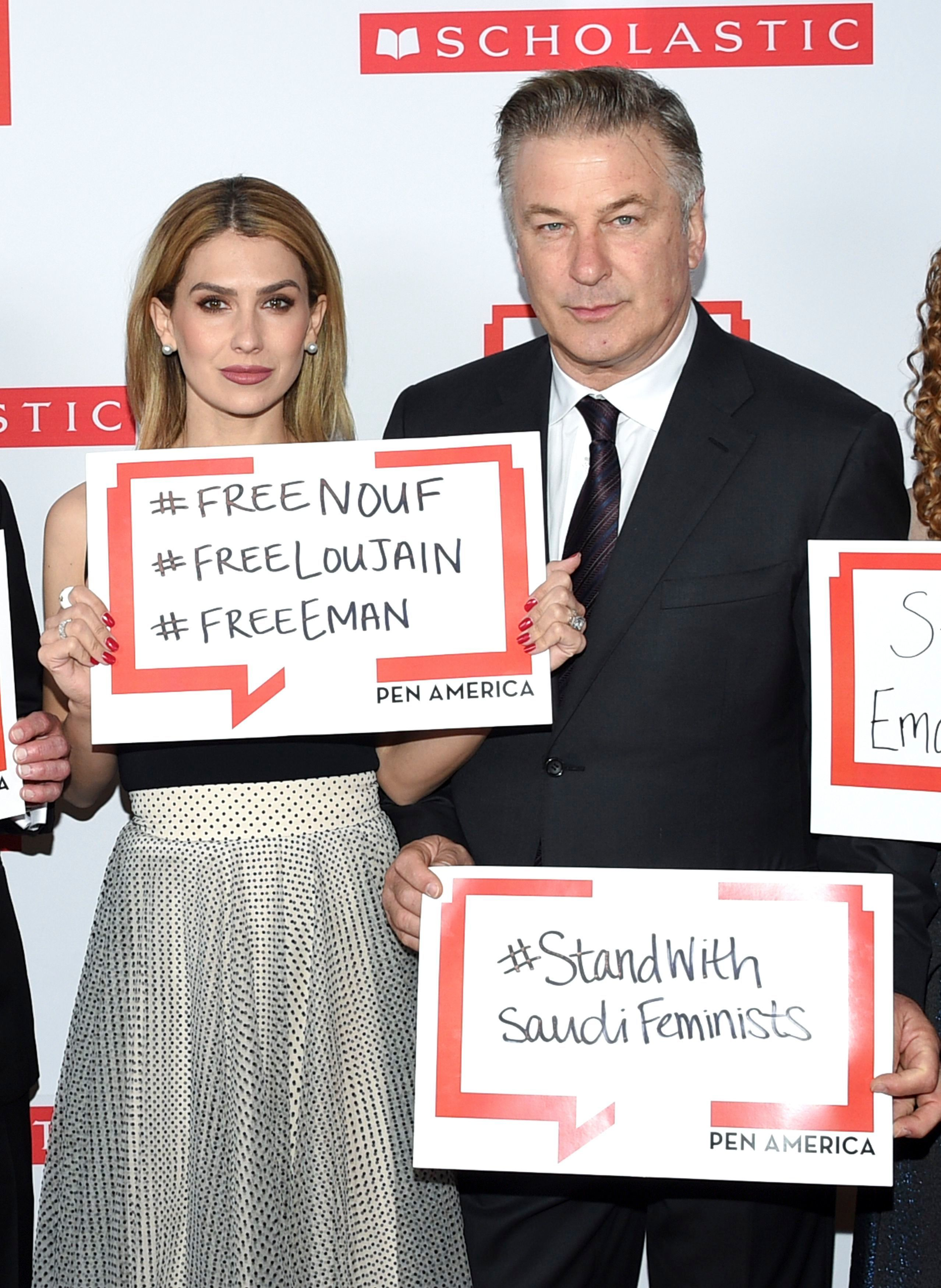 Alec Baldwin and Hilaria Baldwin pose holding signs in support of jailed Saudi women's rights activists Nouf Abdulaziz, Loujain Al Hathloul and Eman Al Nafjan at the 2019 PEN America Literary Gala at the American Museum of Natural History in New York City on May 21, 2019.