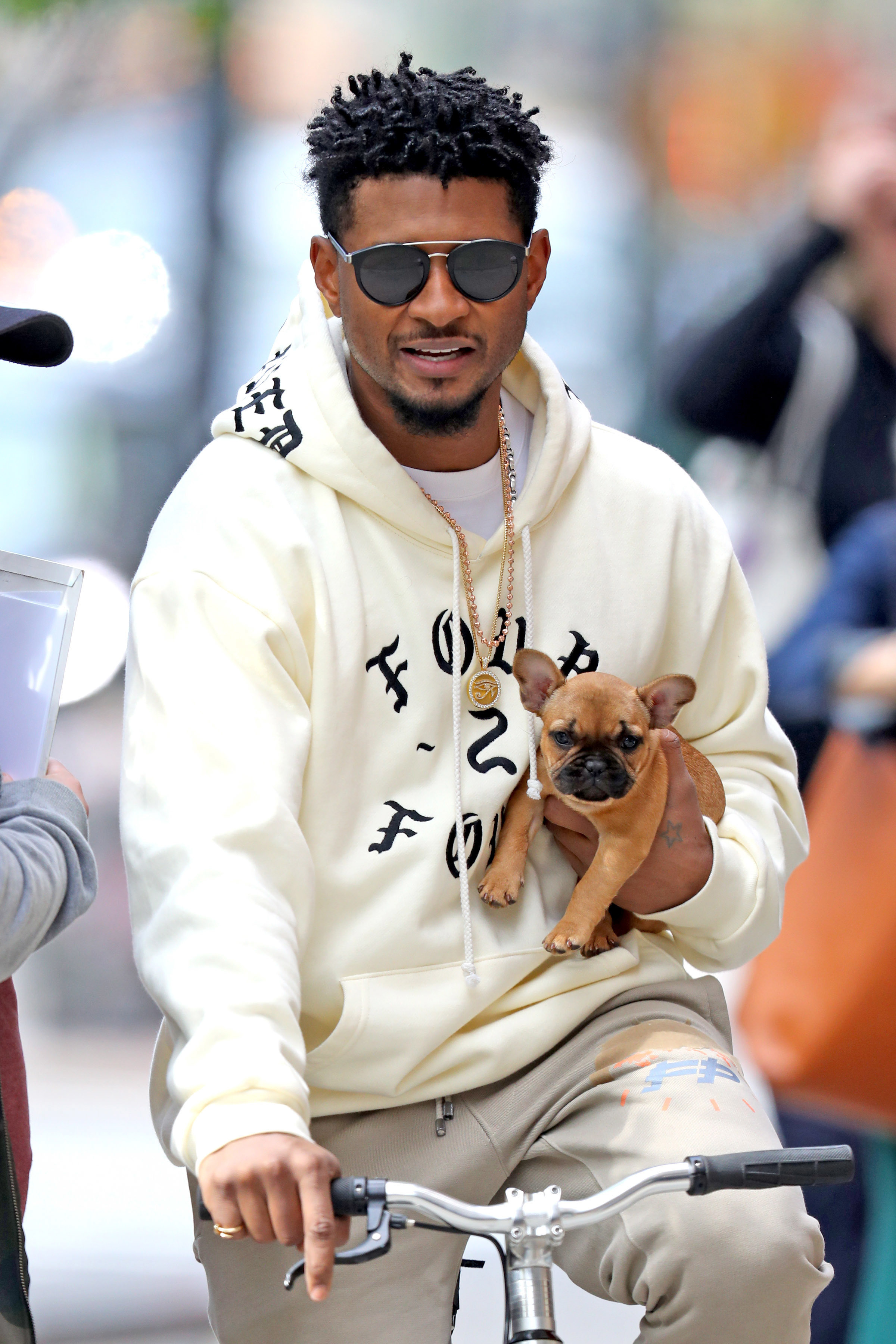 Usher took her new french bulldog puppy on a bike ride while out in New York City on May 7, 2019.