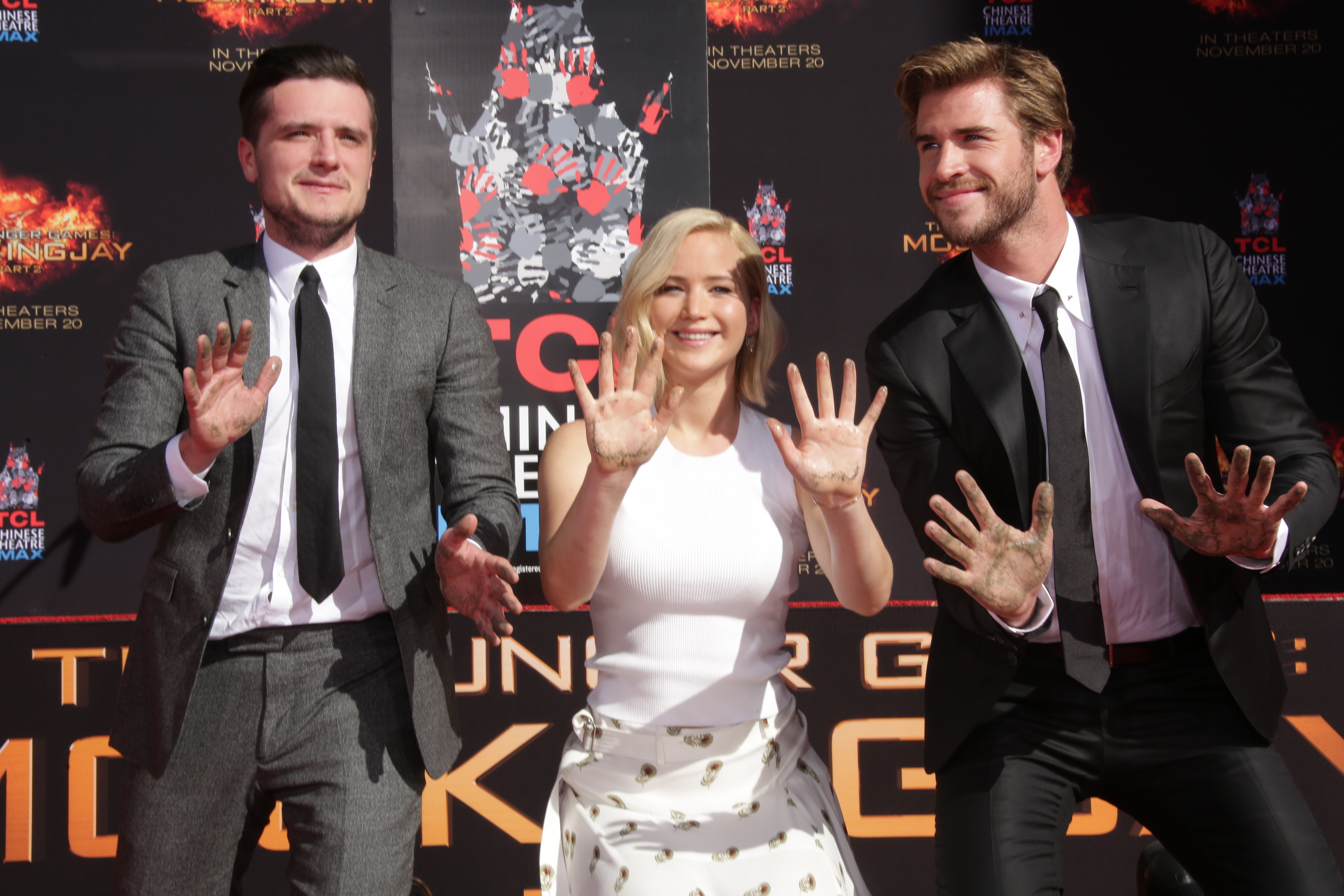 "Josh Hutcherson, Jennifer Lawrence and Liam Hemsworth appear at the ""Hunger Games"" cast hand and footprint ceremony in Los Angeles on Oct. 31, 2015."