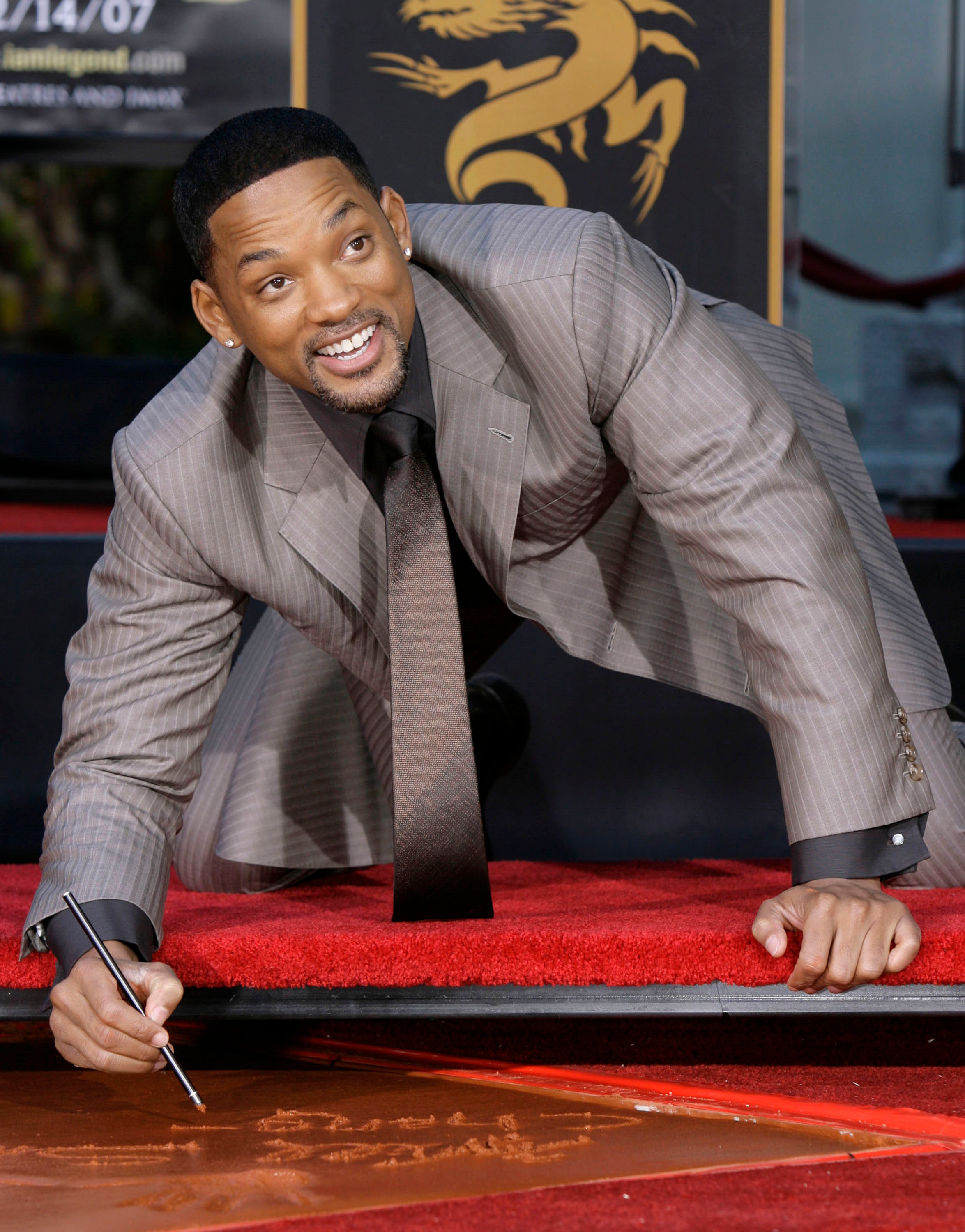 Will Smith signs his name in cement during a hand and footprint ceremony at Grauman's Chinese Theater in Los Angeles on Dec. 10, 2007.