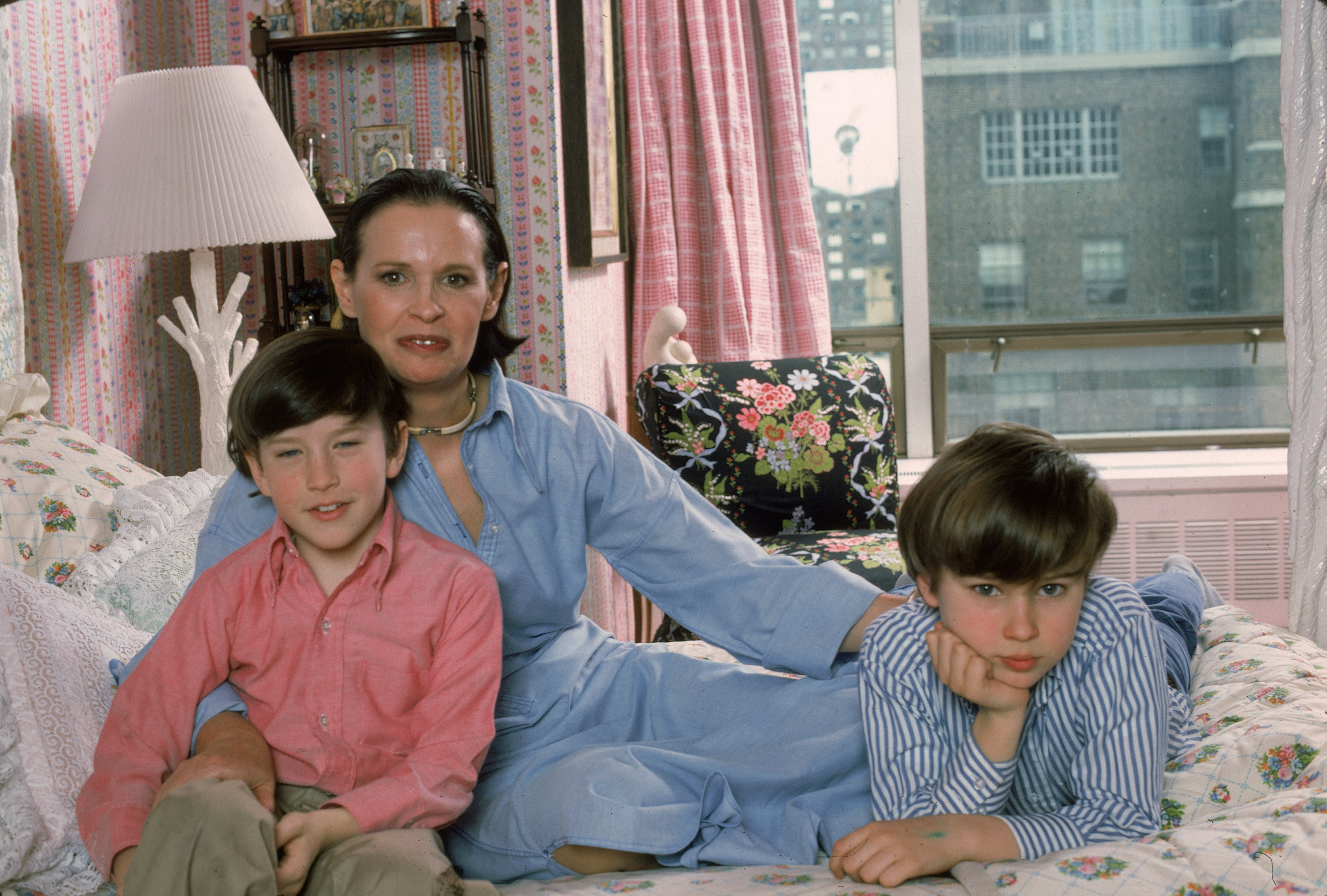 Gloria Vanderbilt poses with sons Anderson Cooper and Carter Vanderbilt Cooper on her bed in their apartment in the UN Towers in New York City in March 1976.