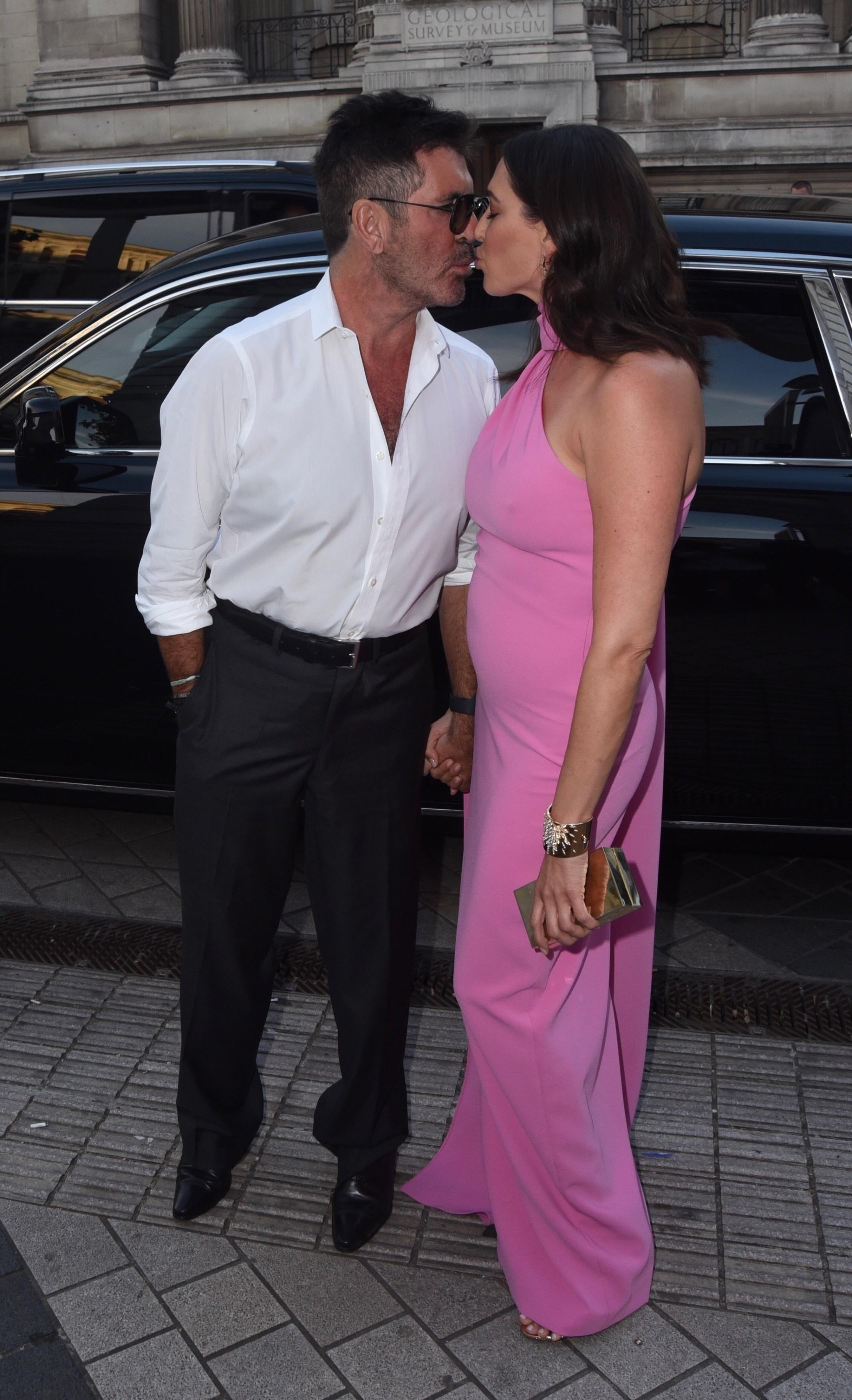 Simon Cowell and  Lauren Silverman were spotted sharing a kiss while arriving at a party in London, England on July 4, 2019.