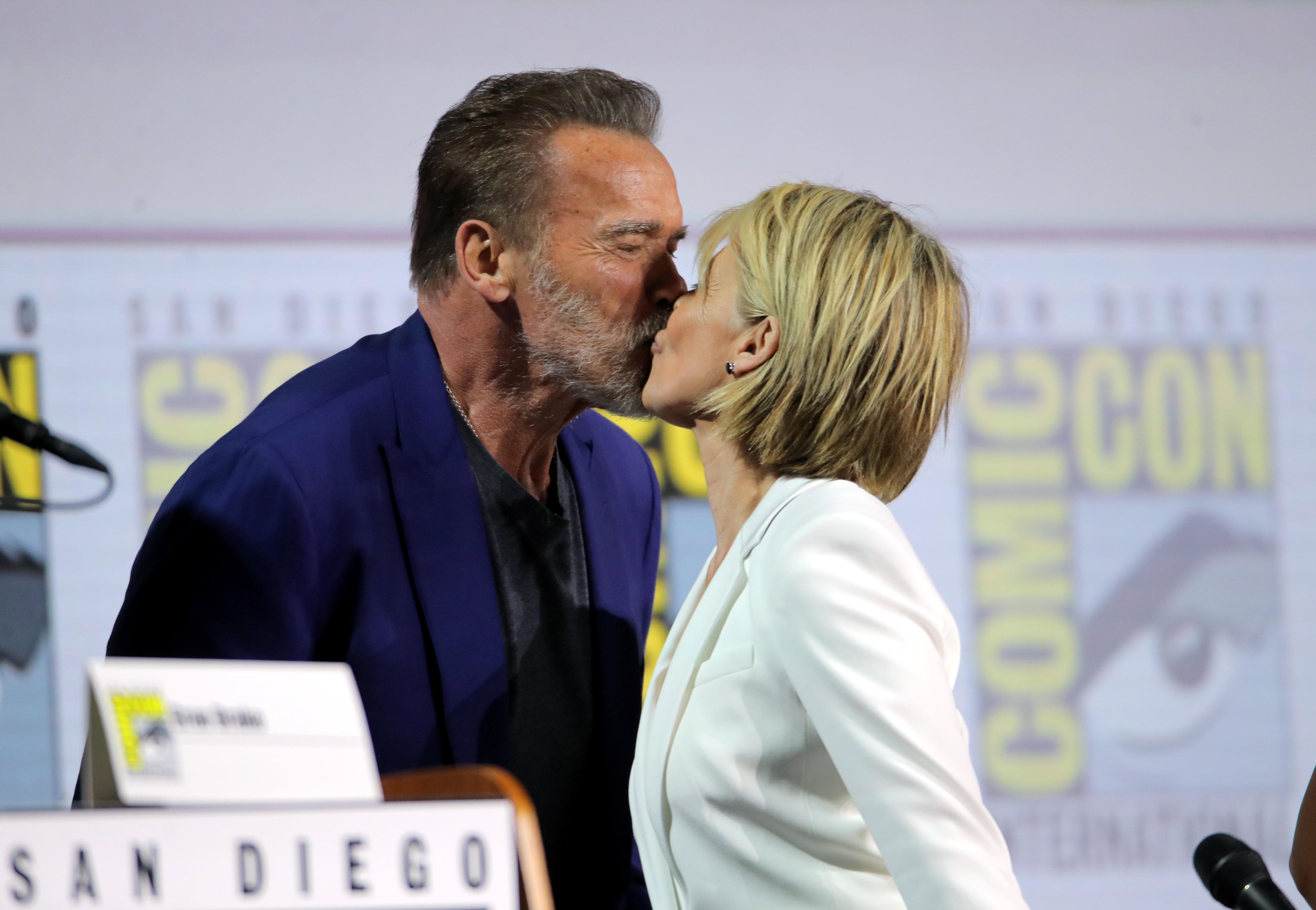 "Arnold Schwarzenegger and Linda Hamilton share a smooch at the ""Terminator: Dark Fate"" film panel at Comic Con International in San Diego, California, on July 18, 2019."